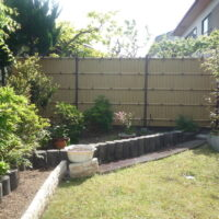 お隣との目かくしに人工竹垣を使い落着いたお庭になりました。